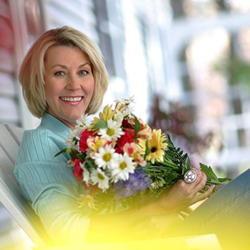 An actual patient of Dr. Gorman's sitting on a porch holding a bouquet of flowers after receiving prepless veneers.