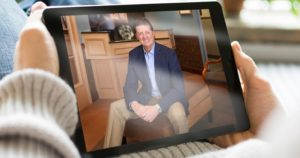 Someone holding an iPad with Dr. Gorman on it for the smile virtual consult