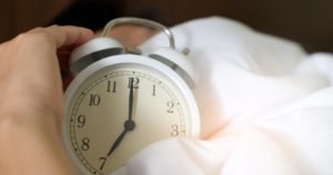 An alarm clock in someone's hands in bed.